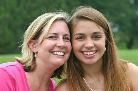 Mother side by side smiling with daughter